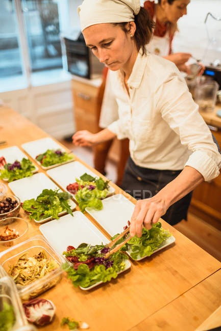 Woman serving plates with salad — Stock Photo