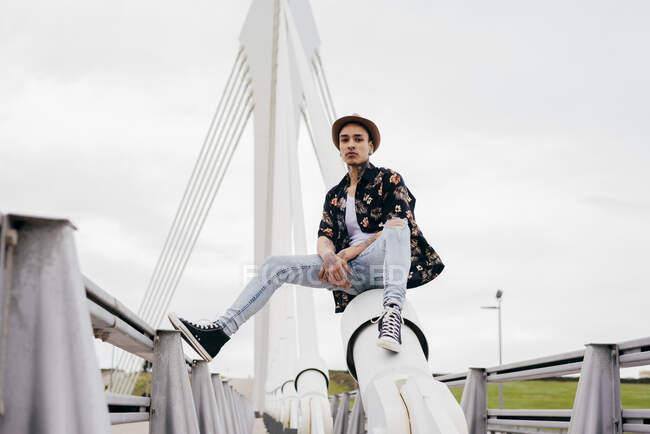 Hipster sentado en la barandilla del puente - foto de stock