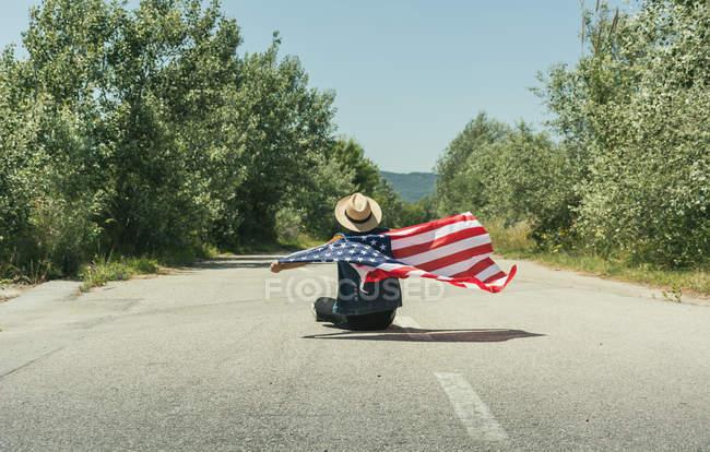 Человек с американским флагом сидит на дороге — стоковое фото
