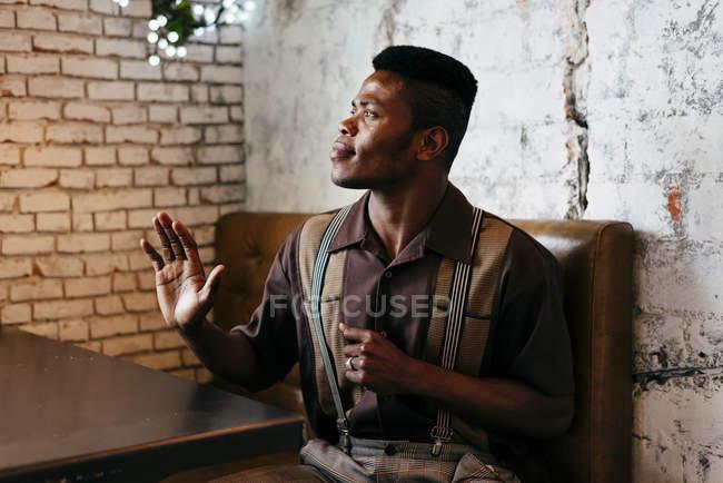 Hombre con ropa clásica sentado en la cafetería - foto de stock
