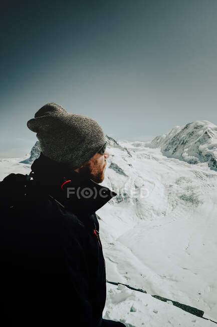 Side view of tourist man standing in the hills and looking away in winter day, Matterhorn (Cervino), Zermatt, Switzerland — Stock Photo