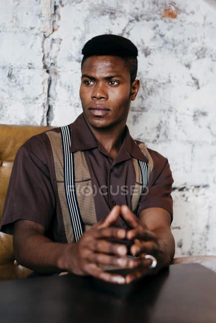 Чорна людина, поклавши руки на стіл — стокове фото