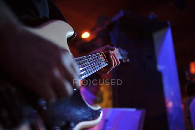 Mani di musicista irriconoscibile in piedi e suonare la chitarra sul palco. — Foto stock