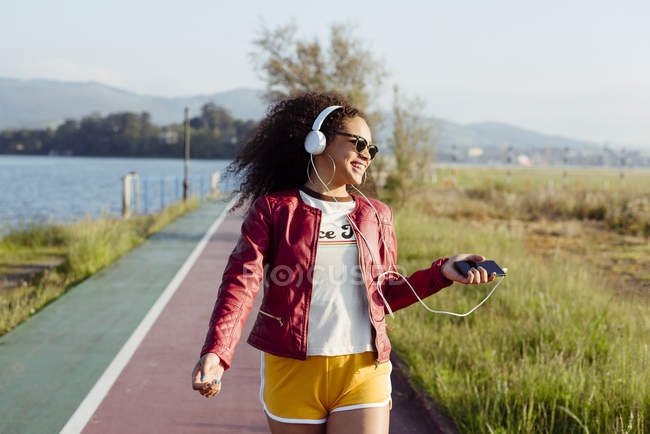 Adolescente escuchando música con auriculares - foto de stock