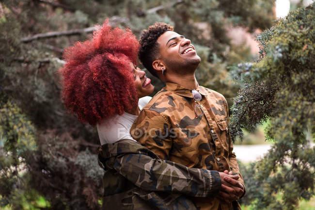 Couple embracing among trees — Stock Photo