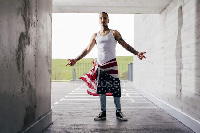 Uomo ispanico con le mani tatuate indossa abiti casual in piedi mostrando ripidità nel parcheggio sotterraneo — Foto stock
