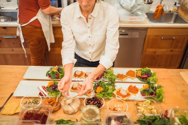 Жінка виступаючої плити з vegan закуски — стокове фото