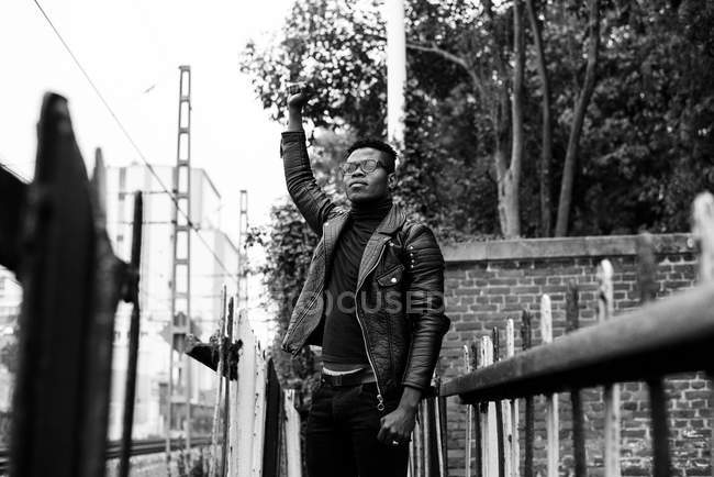 Black man standing on street with hand up — Stock Photo