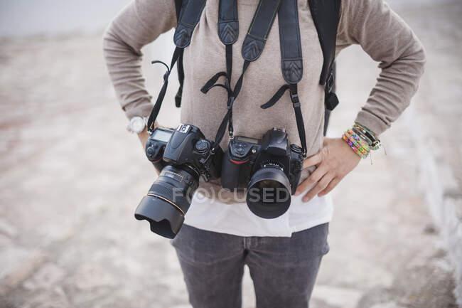 Неузнаваемый фотограф, держащийся за талию и стоящий с камерами на улице. — стоковое фото