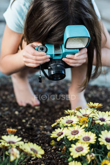 Girl taking photo of flowers — Stock Photo