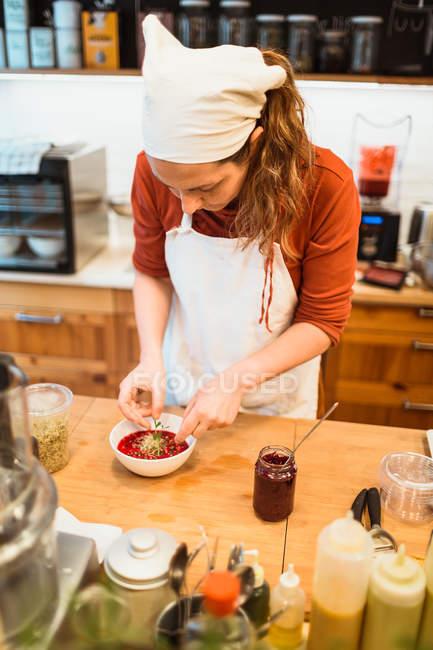 Mulher colocando especiarias para sopa — Fotografia de Stock