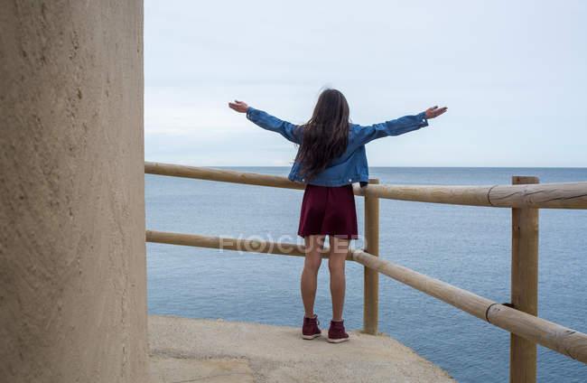 Menina de pé no corrimão à beira-mar — Fotografia de Stock