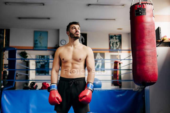 Man standing next to punching bag — Stock Photo