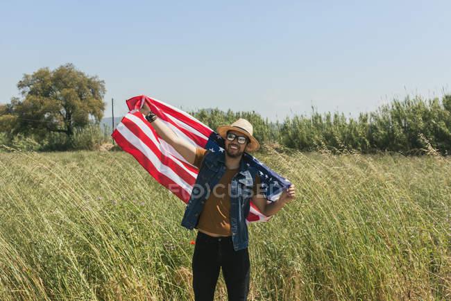 Человек с американским флагом стоит в поле — стоковое фото