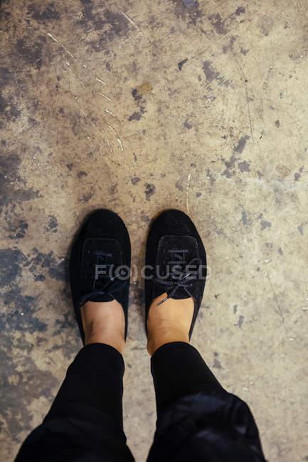 Pés femininos em sapatos no chão gasto — Fotografia de Stock