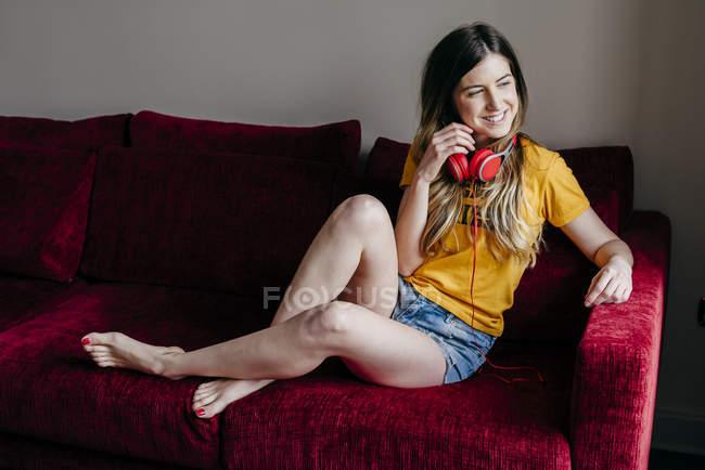 Frau mit Kopfhörern sitzt auf Sofa — Stockfoto
