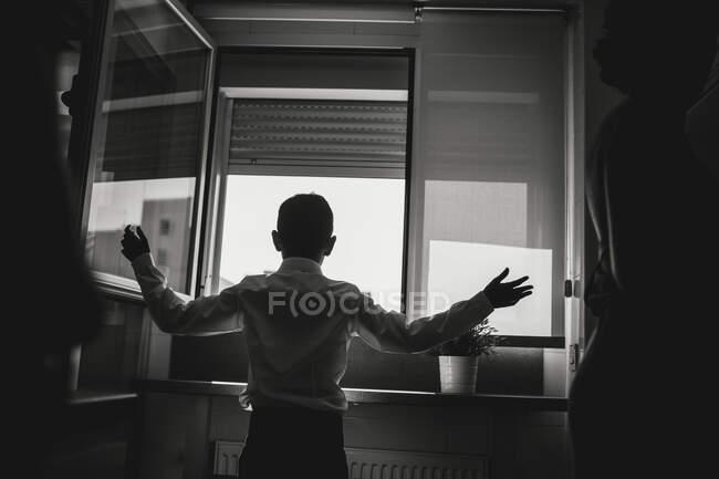 Foto en blanco y negro de la vista trasera del niño de pie en la ventana abierta con las manos separadas. - foto de stock