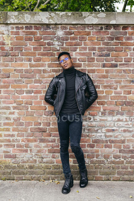 Man standing against brick wall — Stock Photo