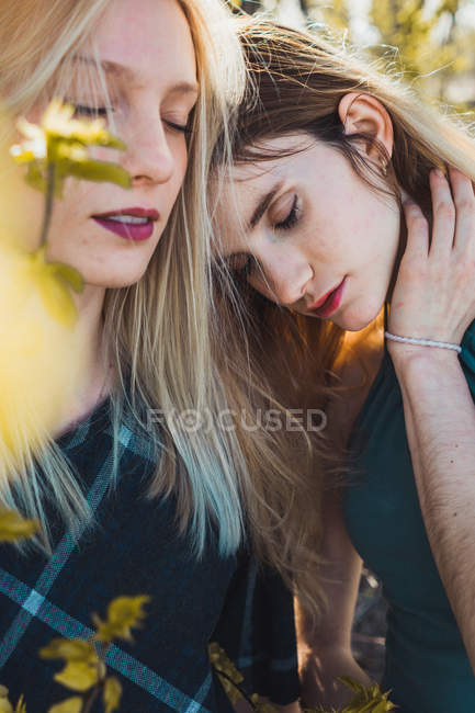 Close-up of young sensual women standing in gentle touch with eyes closed among leaves — Stock Photo
