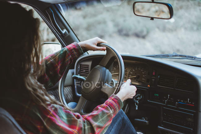 Pretty young unrecognizable woman driving a car in nature — Stock Photo