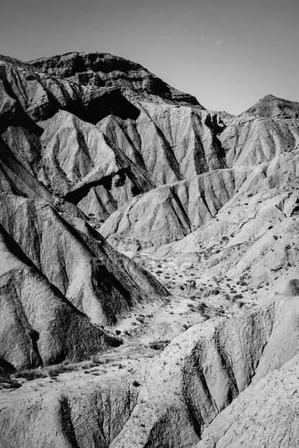 Черно-белый кадр сухих холмов в солнечных лучах. — стоковое фото