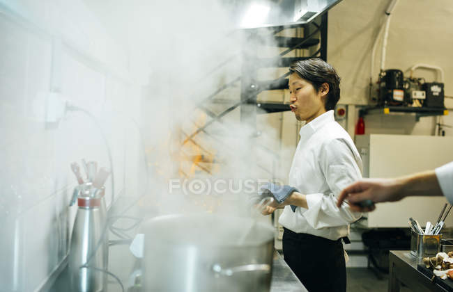 Cook making flambe in restaurant kitchen — Stock Photo