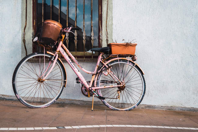 Pink painted rusty vintage bicycle parked at window on street — Stock Photo