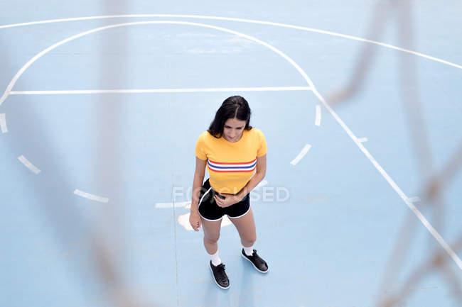 Magro jovem mulher em sportswear pé no chão de esportes azuis — Fotografia de Stock