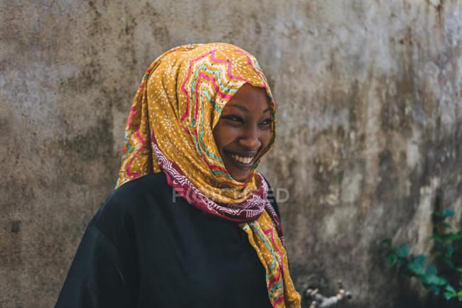 Камерун - Африка - 5 квітня 2018: Посміхаючись молодої жінки африканських у світлі головний убір стояти під грубої стіни. — стокове фото