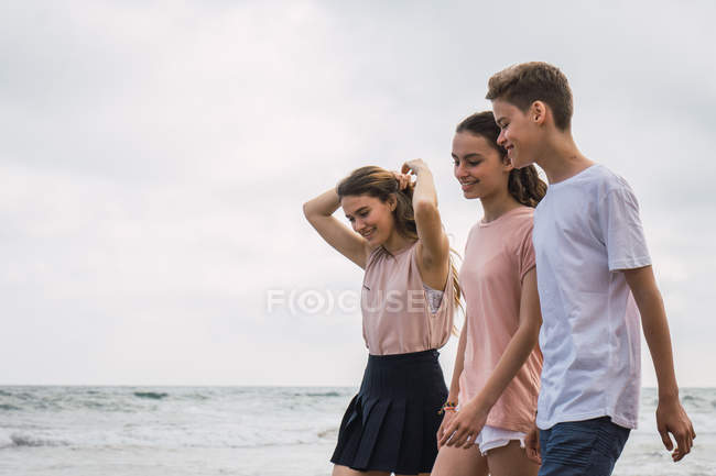 Smiling teenagers walking on beach together — Stock Photo