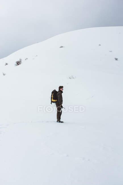 Turista con lo zaino arrampicata sulla montagna nevosa — Foto stock