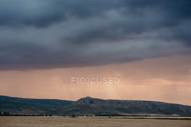 Picturesque view to the field and hills in cloudy gray evening. — Stock Photo