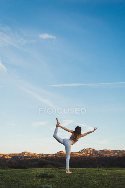 Woman stretching on one leg on lawn in nature — Stock Photo