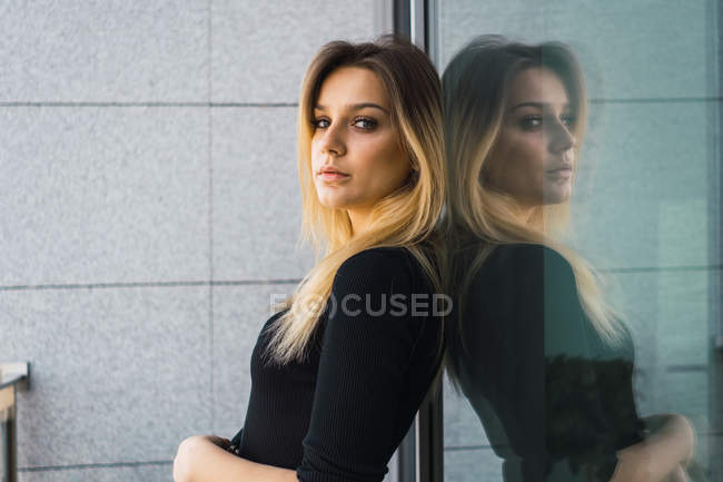 Portrait of confident woman in black leaning on glass wall — Stock Photo