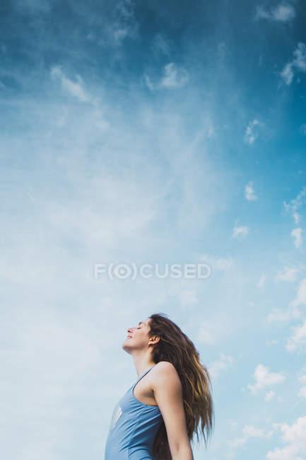 Relaxado jovem mulher em azul maiô de pé contra o céu azul — Fotografia de Stock