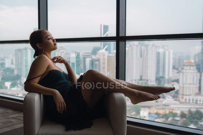 Вродлива жінка розслаблюючим у крісло з видом на місто на тлі — стокове фото