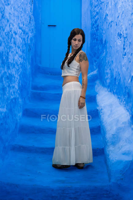Thoughtful woman standing on blue stairs — Stock Photo