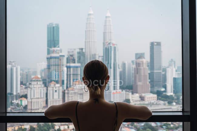 Mujer de pie en casa y mirando a fondo la ventana de los rascacielos - foto de stock