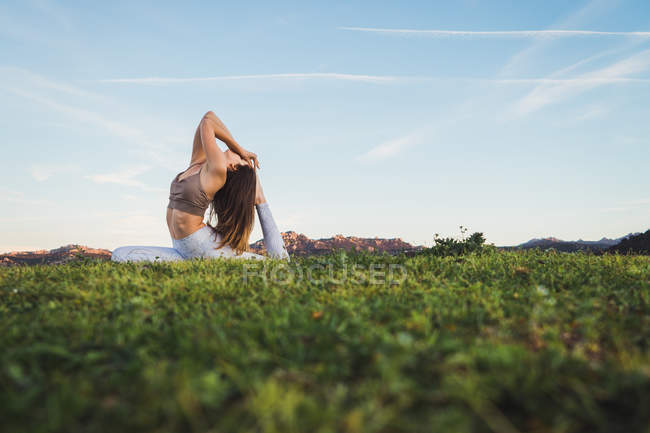 Woman stretching and doing yoga on lawn in nature — Stock Photo
