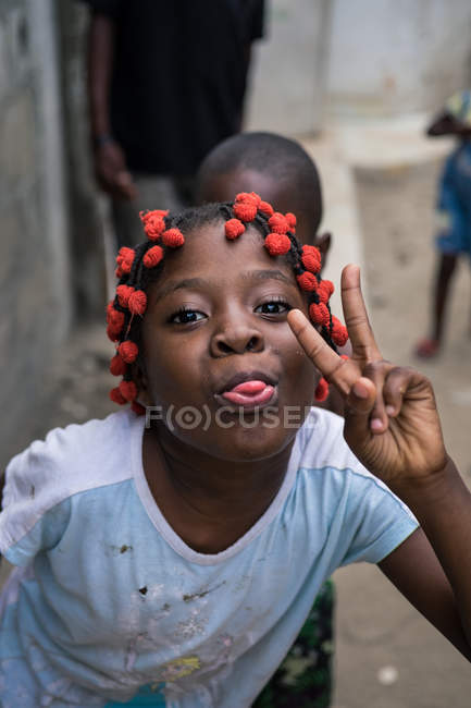 ANGOLA - AFRICA - APRIL 5, 2018 - Ethnic girl showing peace gesture and grimacing with tongue out outdoors — Stock Photo