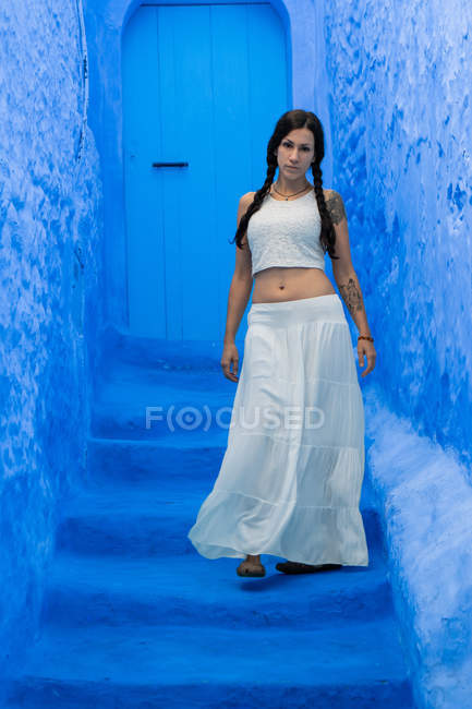 Woman wearing white top and long skirt walking on Moroccan city dyed blue — Stock Photo