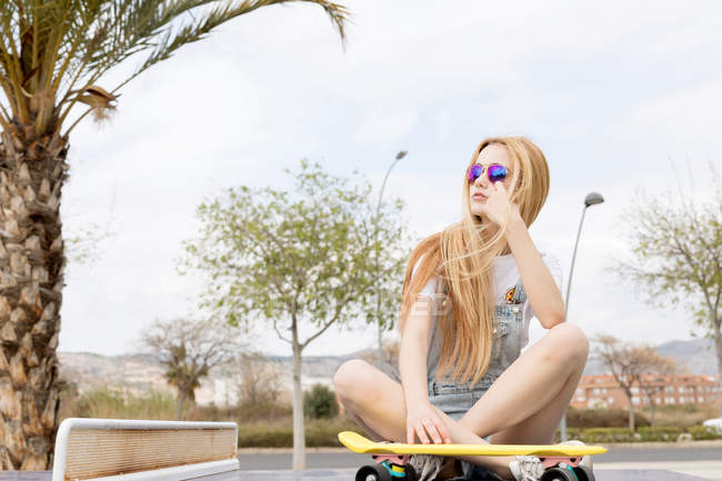 Blonde girl sitting on ground with penny board — Stock Photo