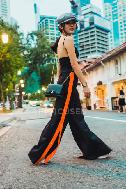 Asian woman in stylish clothes walking on street in city — Stock Photo