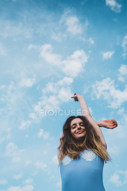 Cheerful young woman in blue swimsuit standing against blue sky — Stock Photo