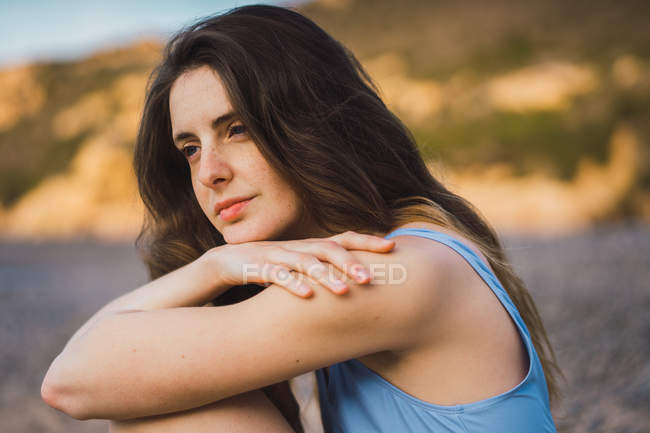 Mujer joven reflexiva en traje de baño sentado en la playa - foto de stock