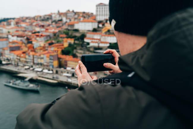 Turista maschio che scatta foto della città vecchia con smartphone, Oporto, Portogallo — Foto stock