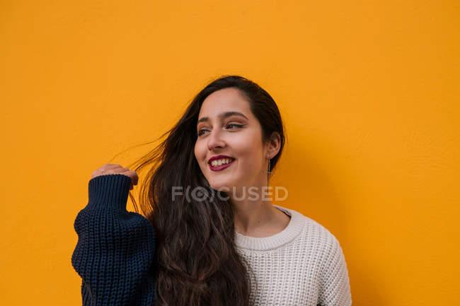 Portrait of smiling teenage girl on orange background — Stock Photo