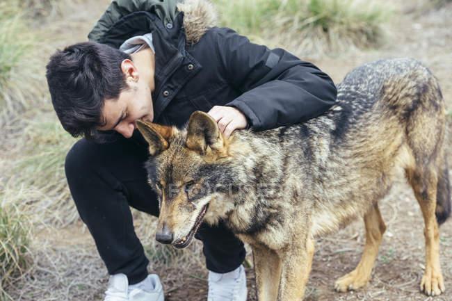 Giovane uomo accarezzando lupo nello zoo — Foto stock