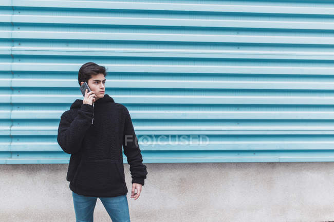 Giovane adolescente in piedi al muro di metallo e parlando su smartphone per strada — Foto stock