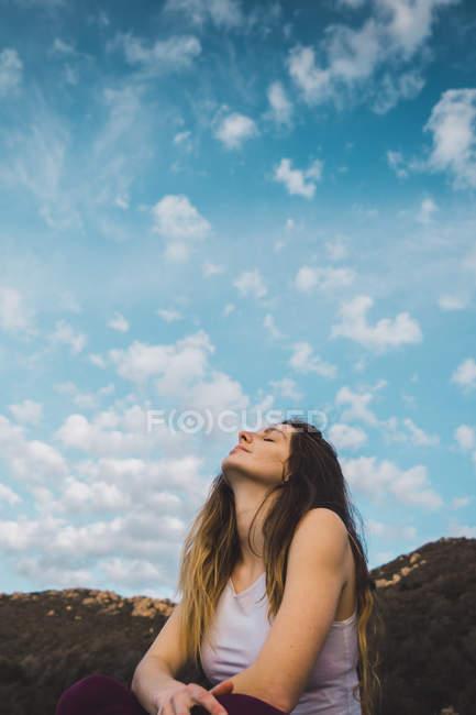Sinnliche Frau sitzt in der Natur unter blauem Himmel — Stockfoto